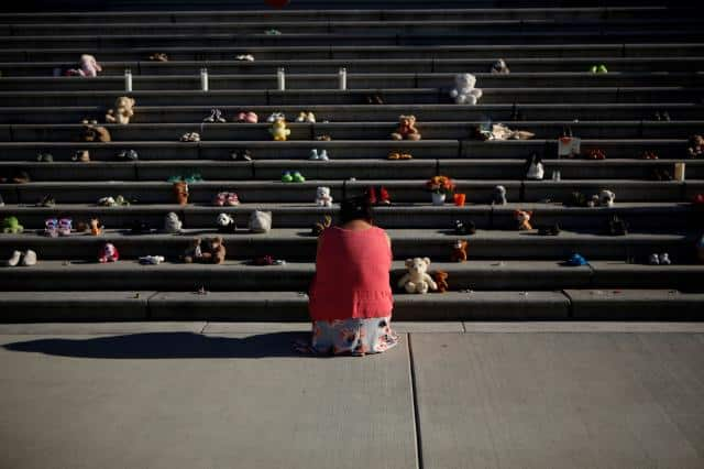 A member of the Tla-O-Qui-Aht First Nation pays her respects below the steps outside the legislature in Victoria on June 1.