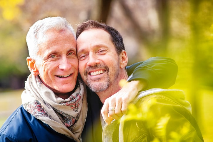 Couple of loving senior gay men portrait in a park in late October. They are both in hip mature fashion, happily and closely looking at the camera.